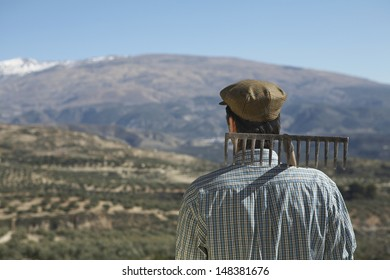 Rear view of middle age farmer with rake on shoulder against mountain