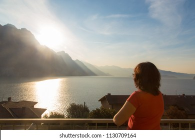 Rear view at middle aged woman standing looking at nature scenery sea and mountains landscape at sunrise meditating and relaxing, travel vacation lifestyle concept. Italy, Lombardia, Riva di Solto