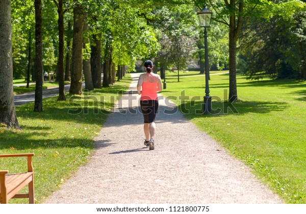 Rear view of a middle aged woman wearing sportswear running in a park