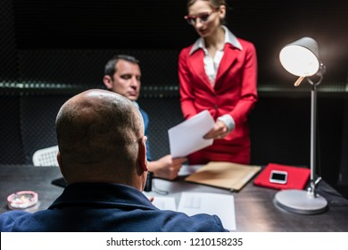 Rear view of a middle-aged suspect or witness sitting at desk during the police interrogation in front of the prosecutor and a female lawyer