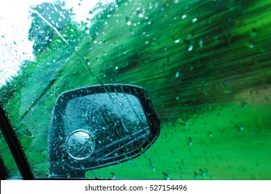 Rear view mirror of a car in motion and rain