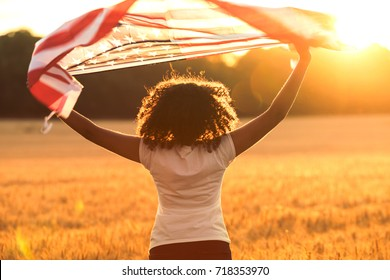 Rear view of mixed race African American girl teenager female young woman in a field holding USA stars and stripes flag above her head in golden sunset evening sunshine