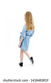 Rear view of modern little girl, standing. Isolated on white background