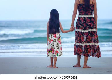 Rear view of a mother and daughter standing on the beach