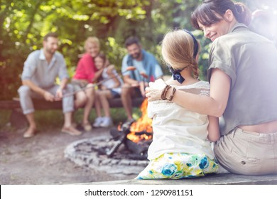 Rear view of mother sitting with arm around daughter while camping at park