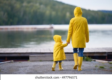 Rear view of mother walking on the beach with her daughter