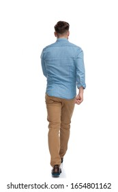 Rear view of a motivated casual man walking on white studio background