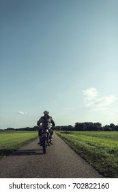 Rear view of motorcyclist riding vintage motorcycle on country road.