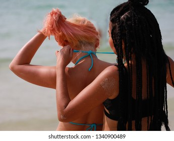 Rear view of multi ethnic young couple woman with bikini Tie straps on the beach