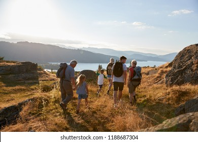 Rear View Of Multi Generation Family Walking On Top Of Hill On Hike Through Countryside In Lake District UK