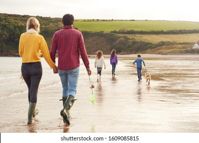 Rear View Of Multi-Cultural Family With Pet Dog Walking Along Beach Shoreline On Winter Vacation