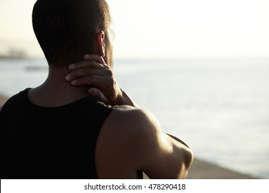 Rear view of muscular dark-skinned man in black A-shirt standing on embankment watching sun setting over horizon, thinking over problems in his life, rubbing his neck during evening walk. Flare sun