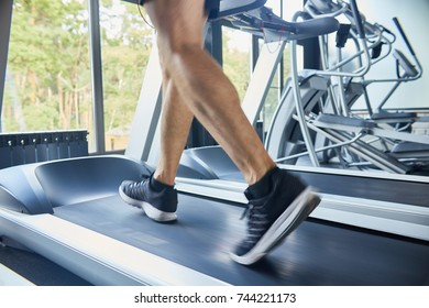 Rear view of muscular male legs  running on treadmill in modern gym during cardio workout against window