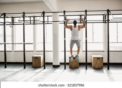 Rear view of muscular man doing pull ups at the gym