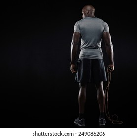 Rear view of muscular man standing with jumping rope on black background. Studio shot of fitness model holding skipping rope looking at copy space.