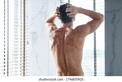Rear view of muscular man washing hair and body, standing under the water in bathroom