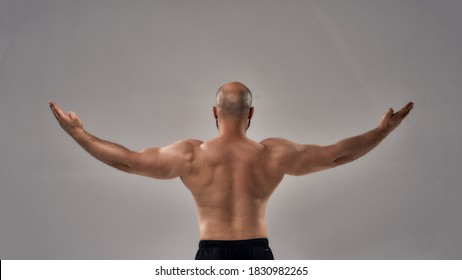 Rear view of muscular strong man with naked torso standing with outstretched arms isolated over grey background. Sport, bodybuilding, workout concept