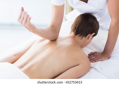 Rear view of naked woman receiving back massage at spa