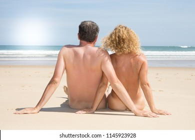 Rear view of a naturist couple man and woman nudism on the beach
