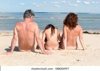 Rear view of a naturist family on the beach