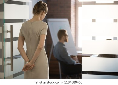 Rear view at nervous woman standing at door waiting focused on speech preparation for important meeting negotiation feeling panic stress or lack of confidence thinking of public speaking fear concept