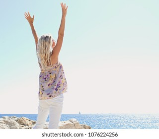 Rear view of nordic tourist woman on cliff rock by blue sea and sky, stretching arms up, outdoors nature freedom. Healthy female enjoying healthy living holiday, travel leisure recreation lifestyle.