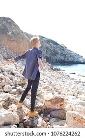 Rear view of nordic tourist young man on coastal beach destination, contemplative stretching arms against sunny sky on summer holiday, nature outdoors. Healthy leisure recreation lifestyle, exterior.