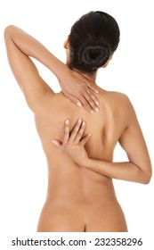 Rear view of nude woman with back pain.