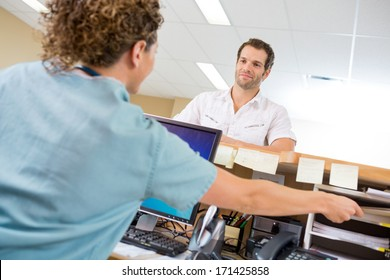 Rear view of nurse assisting man while working at reception desk in hospital