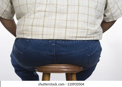 Rear view of an obese man sitting on a stool isolated over white background
