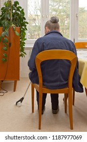Rear view of an old woman sitting at a table picking up something, that has fallen on the floor, with a long-reach grabber device for elderly or disabled people.