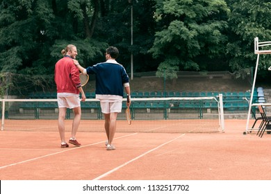 rear view of old-fashioned friends with wooden rackets walking on tennis court