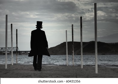 Rear view on alone man in the black coat and top-hat going to the sea. Natural darkness. Artistic colors added