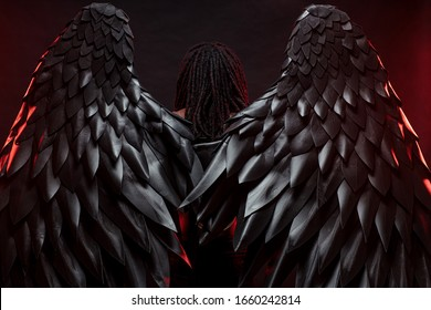 rear view on back of dark angel with big black wings, angel with dreadlocks stand isolated over black background, red neon lights reflected on wings. fancy, unusual and interesting photoshoot