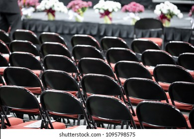 Rear view on rows of black folding chairs, with a stage in the background, at a high school or college gradution, with space for text on top