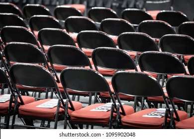 Rear view on rows of black folding chairs, with red cushions, at a gradution ceremony, with space for text on top