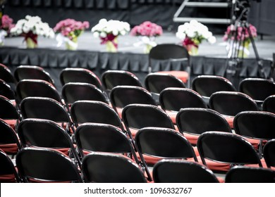 Rear view on rows of black folding chairs, with a stage in the background, at a gradution or church ceremony, with space for text on top