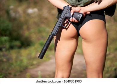 rear view on sportive athletic woman's legs in shorts, armed female is going to shoot a gun