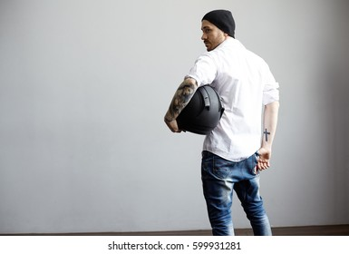 Rear view on tattooed body man in white shirt and black hat. Athletic biker looking back and holding blank black motorcycle helmet. Free space for advertising product and promotional text