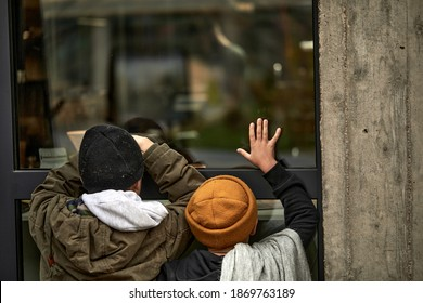 rear view on two poor homeless children leaned on window of building, need shelter and food