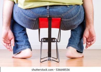 Rear view of overweight barefoot man sat on tiny chair