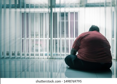 Rear view of overweight man looks depressed while sitting near the window