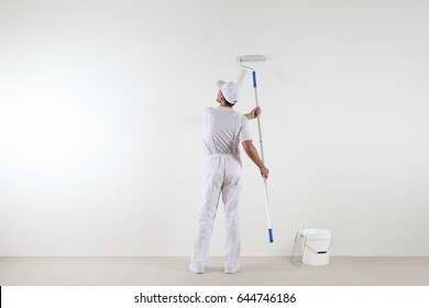 Rear view of painter man looking at blank wall, with paint stick roller and bucket, isolated on white room