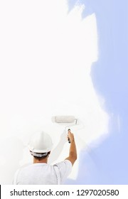 Rear view of painter man with paint roller painting on blank wall, isolated on white, copy space template