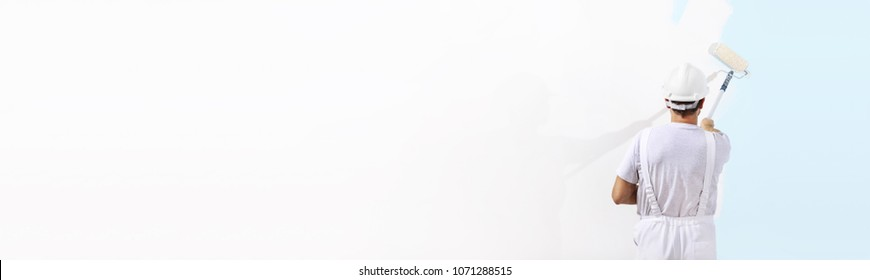 Rear view of painter man painting the blue on blank wall, with paint roller  isolated on white big copy space