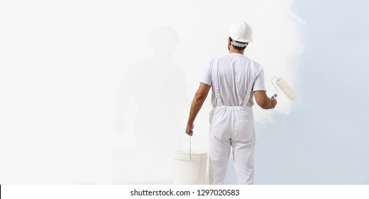 Rear view of painter man painting the wall, with paint roller and bucket, isolated on big empty white copy space template