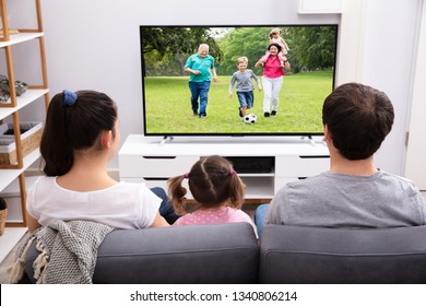 Rear View Of Parents Sitting With Her Daughter Watching Television At Home