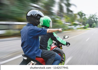 Rear view of passenger directing the way to motorcycle taxi driver on the street