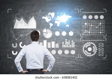 Rear view of a pensive businessman looking at glowing graphs and a world map at a blackboard in class. Toned image. Elements of this image furnished by NASA
