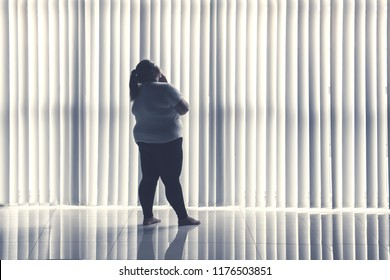 Rear view of a pensive obese woman standing by the window. Shot at home